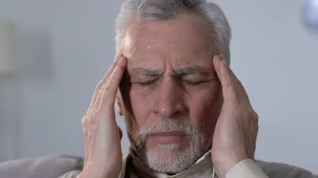 migrén : Elderly man massaging temples, suffering from migraine disorder, health problems