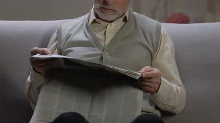 hírlevél : Senior man sitting on sofa at home, reading latest daily news in printing media