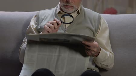 hírlevél : Aged male sitting on sofa, reading newspaper article with magnifying glass Stock mozgókép
