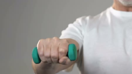 функция : Elderly man with trembling hands lifting dumbbell, rehabilitation after trauma