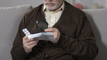 nyugta : Old male with magnifying glass reading pills dosage and precautions, treatment Stock mozgókép