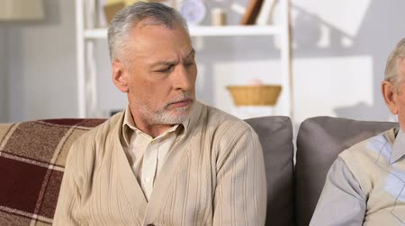 misunderstood : Offended male pensioners looking each other reading books sitting sofa, conflict