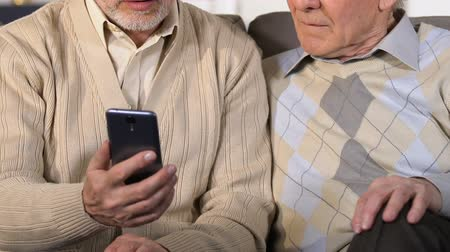 inline : Two old men using smartphone closeup, mobile banking application, technology