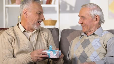 emeryt : Male pensioner presenting gift box to friend, birthday surprise, congratulation