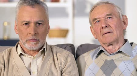 bezrobotny : Sad male pensioners looking camera closeup, old friend lost, retirement poverty