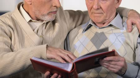 photo album : Two male friends looking photo album hugging, old time memories, nostalgia Stock Footage