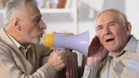 perguntando : Aged man listening to friend shouting in megaphone, deafness disease, health