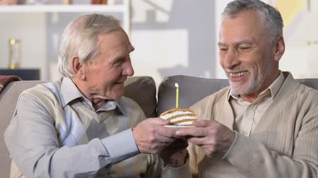 шестидесятые годы : Senior man presenting birthday cake with candle, friendship connection, surprise Стоковые видеозаписи