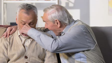 travessura : Playful senior man joking with friend pinching nose, old age positivity, humor