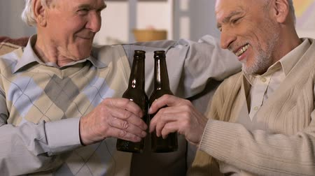 шестидесятые годы : Old men drinking beer sitting sofa, friends clinking bottles enjoying weekend