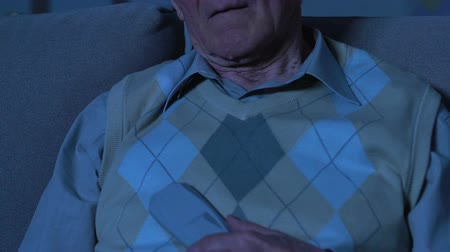 tiredness : Male pensioner sleeping front tv sitting on sofa closeup, having nap, tiredness Stock Footage