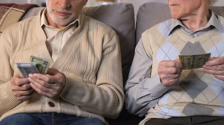 пожертвование : Sad senior men counting money sitting on sofa closeup, low living standard