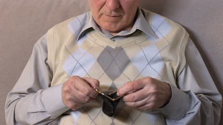пожертвование : Aged male showing empty wallet camera, pension reform, retirement bankruptcy.