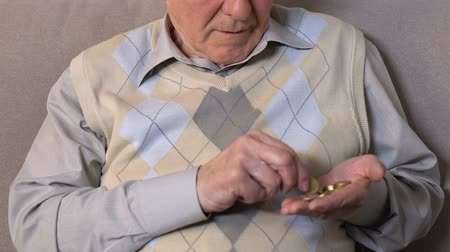 cent : Old man counting coins hand looking camera, pension fund, poverty hopelessness Stock Footage