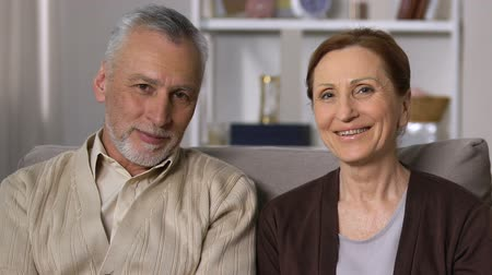 életerő : Happy retired couple looking camera sitting sofa, old age vitality, health