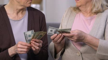 tariff : Sad senior ladies counting dollar banknotes, high interest rate for crediting