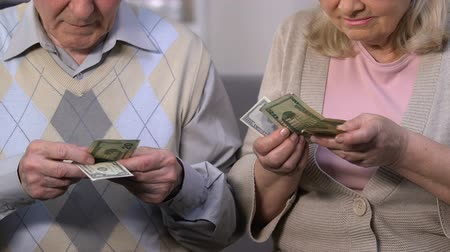 economics : Sad senior couple counting dollars, pension reform, social guarantees for old