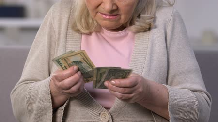 tariff : Upset elderly woman counting dollar banknotes, low retirement payment, pension