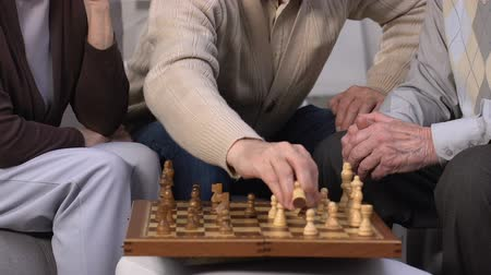 companionship : Group of seniors playing chess at nursing home, enjoying leisure time together Stock Footage
