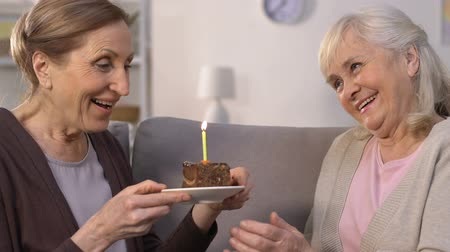 nursing : Elderly woman gifting birthday cake to friend, lady making wish and blows candle Stock Footage