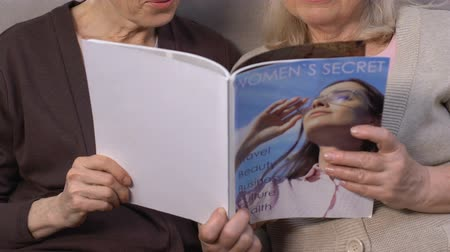 kafeterya : Elderly modern women reading magazine, searching for beauty recipe, cosmetology Stok Video