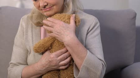 плюшевый мишка : Lonely aged mother embracing teddy bear, remembering busy children, memories Стоковые видеозаписи