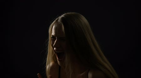 hidden face : Frightened woman screaming and closing face with hands against black background Stock Footage