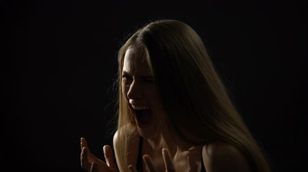 relieve : Angry woman screaming against dark background, relieving stress, depression