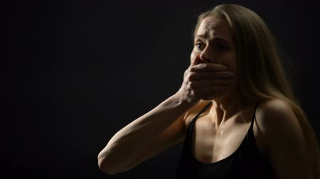 успокаивающий : Woman shouting against dark background, closing mouth with hand, calming down