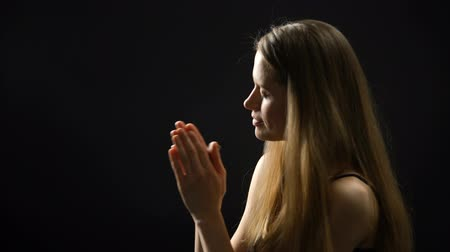 megváltás : Blonde woman praying to God, holding cross in hands, faith and spirituality