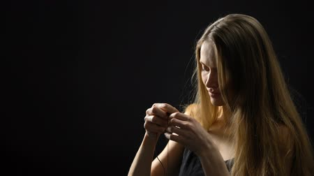 megváltás : Young woman putting on necklace with cross, accepting God, religion and faith