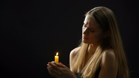 repentance : Religious woman blowing out candle after prayer, deep faith and repentance Stock Footage