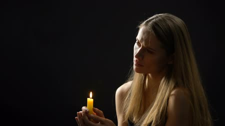 repentance : Weak blonde woman holding candle in hands and praying, asking God for health Stock Footage