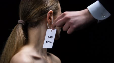 perverso : Male hand putting bad girl label on female ear, stereotypes about women behavior