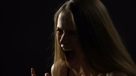 sní : Young woman shouting in despair, revealing stress and negative emotions.