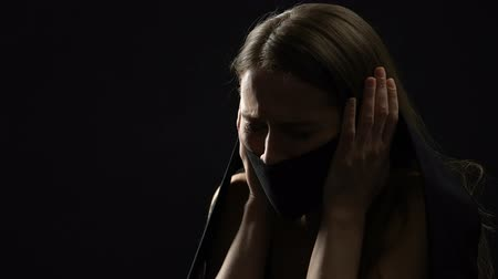 oppression : Depressed female closing mouth with dark fabric, suppressing emotions, sexism Stock Footage