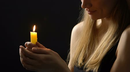 personalità : Peaceful smiling lady holding burning candle hoping for better, faith and belief Filmati Stock