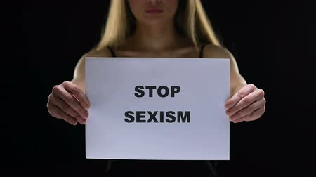 feminist : Feminist lady holding stop sexism sign, prevent social inequality, female rights Stock Footage