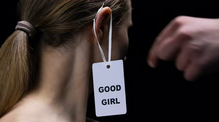 verguenza : Male hanging good girl label on female ear, submission to man rules, disrespect Archivo de Video