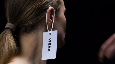 ear protection : Male hand hanging weak label on female ear, underscoring personal qualities
