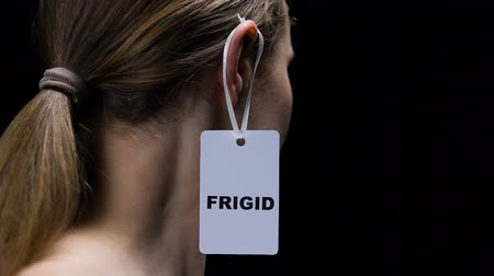 ear protection : Male hand hanging frigid label on female ear, humiliating personality, offence Stock Footage