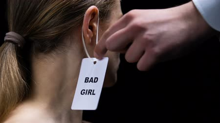 ear protection : Male hand hanging bad girl label on female ear, social disrespect and submission