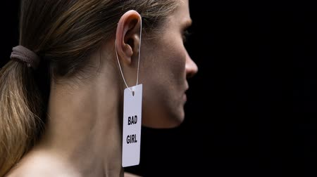 ear protection : Lady tearing bad girl label from ear, protest against shaming and labeling Stock Footage