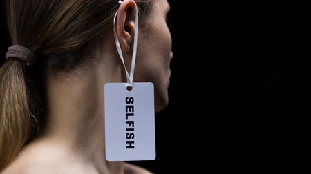 ear protection : Man hand hanging selfish label on female ear, showing disrespect and shaming