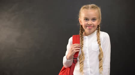 subject : Smiling girl with rucksack smiling on camera on blackboard background, education Stock Footage