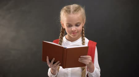 klasa : Happy female child reading book and smiling on camera, education, love to school