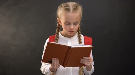 subject : Smart female kid reading book, blackboard on background, thirst for knowledge Stock Footage