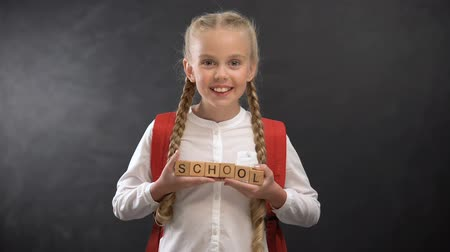 elsődleges : Joyful female child holding wooden cubes with school word, first-former kid