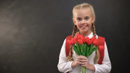 klasa : Pretty female first-grader holding tulips bouquet against blackboard background Wideo