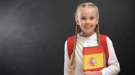 subject : Smiling schoolgirl holding Spanish language book against blackboard background